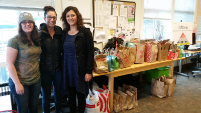 """Andrea Carranza, Camelia Yavrom and a staff member from the """"Life Moves"""" homeless shelter stand in front of donated items."""
